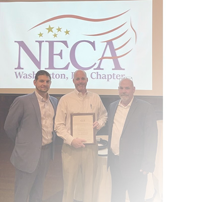 Three men in front of NECA DC Logo, Mona representative holding anniversary plaque.